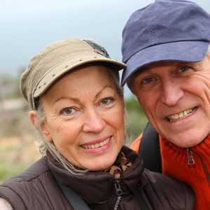 Older couple smiling while on a hike
